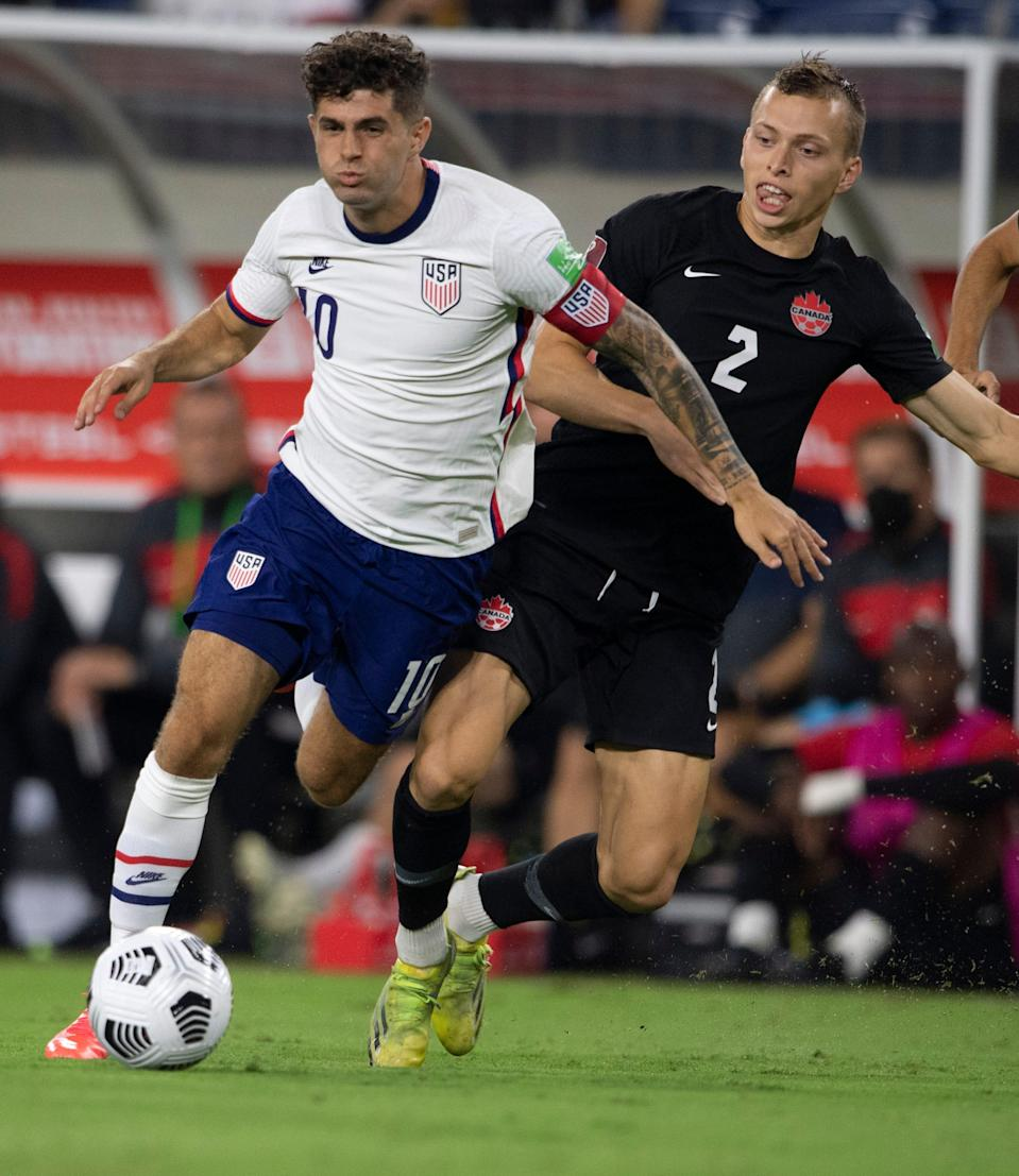 United States forward Christian Pulisic (10) and Canada defender Alistair Johnston (2) battle for the ball during the first half at Nissan Stadium.