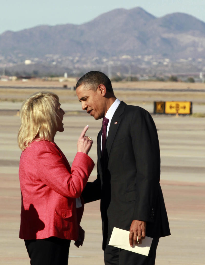 "Arizona Gov. Jan Brewer points at President Barack Obama after he arrived at Phoenix-Mesa Gateway Airport, Wednesday, Jan. 25, 2012, in Mesa, Ariz. Brewer greeted Obama and what she got was a book critique. Of her book. The two leaders engaged in an intense conversation at the base of Air Force One's steps. Both could be seen smiling, but speaking at the same time. Asked moments later what the conversation was about, Brewer, a Republican, said: ""He was a little disturbed about my book."" Brewer recently published a book, ""Scorpions for Breakfast,"" something of a memoir that describes her years growing up and defends her signing of Arizona's controversial law cracking down on illegal immigrants, which Obama opposes. Brewer also handed Obama an envelope with a handwritten invitation for Obama to return to Arizona to meet her for lunch and to join her for a visit to the border.  (AP Photo/Haraz N. Ghanbari)"