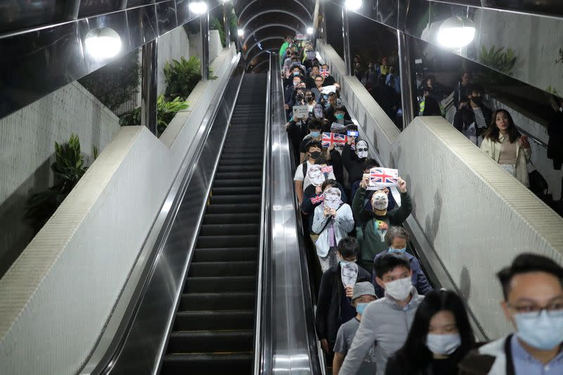 Anti-government protesters wearing masks depicting Simon Cheng, a former British Consulate employee, ride an escalator at a shopping mall during a rally in Hong Kong