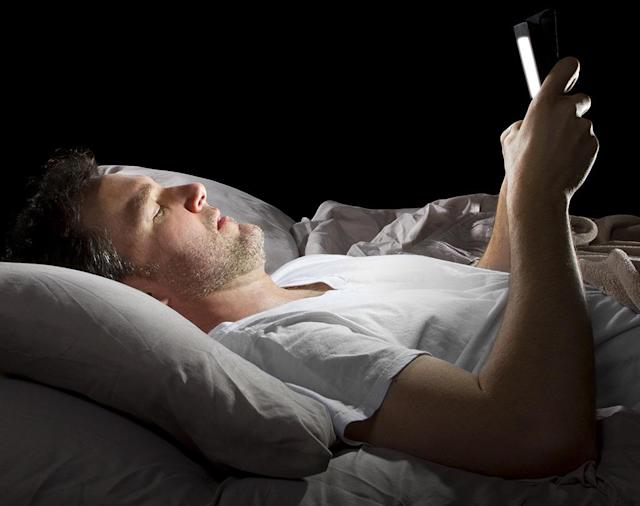 man on phone in bed