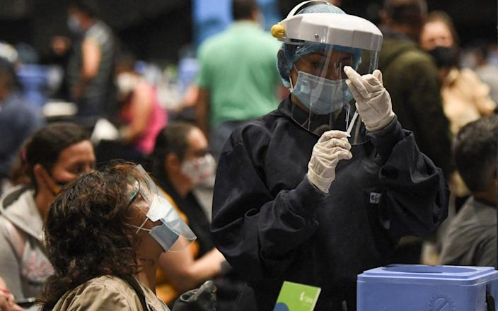 A health worker prepares a dose of the Pfizer-BioNTech vaccine against COVID-19 to inoculate a woman in Bogota, on June 16, 2021. - Colombia has officially recorded more than 90,000 Covid-19 deaths. - AFP