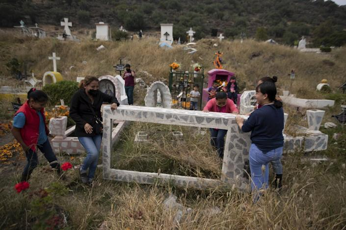 People lift up a gravestone to clean it