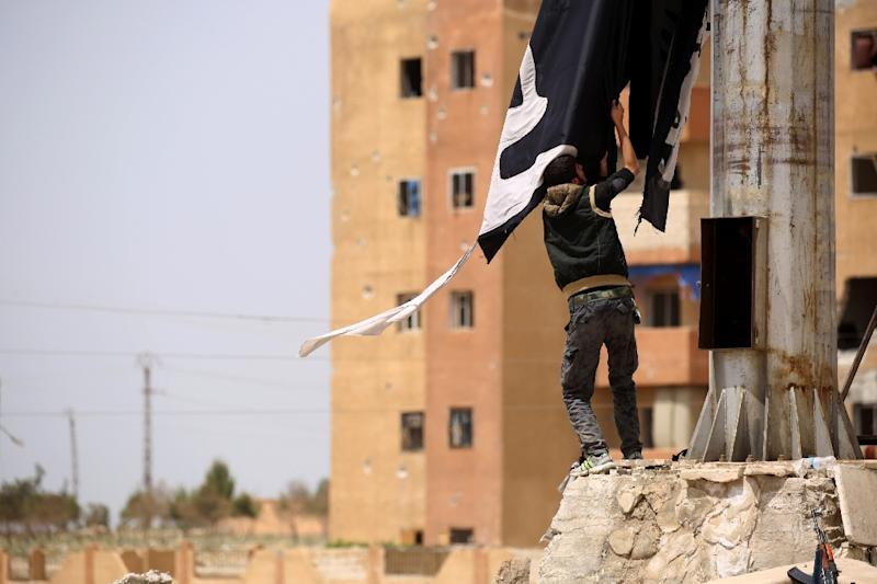 A member of the US-backed Syrian Democratic Forces (SDF) removes an Islamic State group flag in the northern town of Tabqa on April 30, 2017 after capturing it from the jihadists (AFP Photo/DELIL SOULEIMAN)