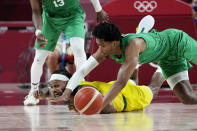 Australia's Patty Mills, left, and Nigeria's Chikezie Okpala, right, scramble for a loose ball during a men's basketball preliminary round game at the 2020 Summer Olympics, Sunday, July 25, 2021, in Saitama, Japan. (AP Photo/Eric Gay)