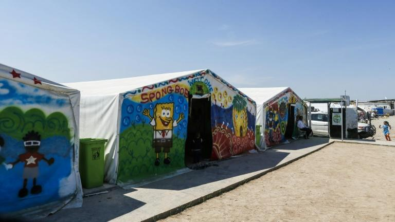 Facilities at Hasan Sham camp for the displaced, east of Mosul, are basic, the tents daubed with bright murals, technicolour handprints and SpongeBob SquarePants