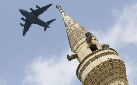 A U.S. Air Force Boeing C-17A Globemaster III large transport aircraft flies over a minaret after taking off from Incirlik air base in Adana, Turkey, in this August 12, 2015 file photo. REUTERS/Murad Sezer/Files