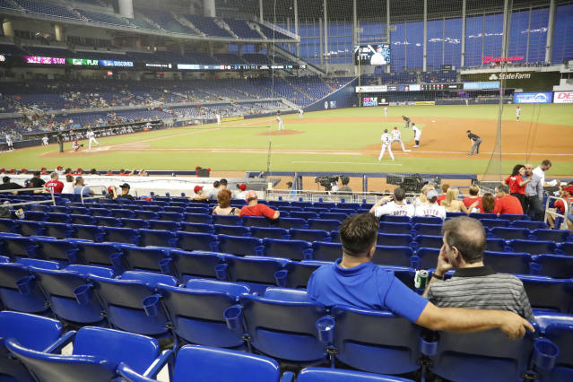 FILE - In this Monday, Aug. 26, 2019 file photo, fans watch play among empty seats during the second inning of a baseball game between the Miami Marlins and the Cincinnati Reds in Miami. Many college and pro sports teams already were dealing with declining ticket sales. The improved at-home experience, the emergence of wide-spread legalized betting and the changing social makeup of fan bases have been catalysts, while dynamic pricing, increases in parking and concession prices and a push toward luxury seating have exacerbated the problem. (AP Photo/Wilfredo Lee, File)