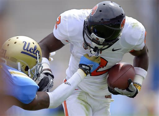 Oregon State wide receiver Markus Wheaton, right, gets a face mask as he runs the ball from UCLA cornerback Aaron Hester during the first half of their NCAA college football game, Saturday, Sept. 22, 2012, in Pasadena, Calif. (AP Photo/Mark J. Terrill)