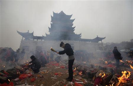 Worshippers burn incense to pray for wealth on the fifth day of Chinese Lunar New Year, which is believed to be the day for welcoming the God of Wealth into households, at the Guiyuan Buddhist Temple in Wuhan, Hubei province in this February 14, 2013 file photo. REUTERS/Darley Shen/Files
