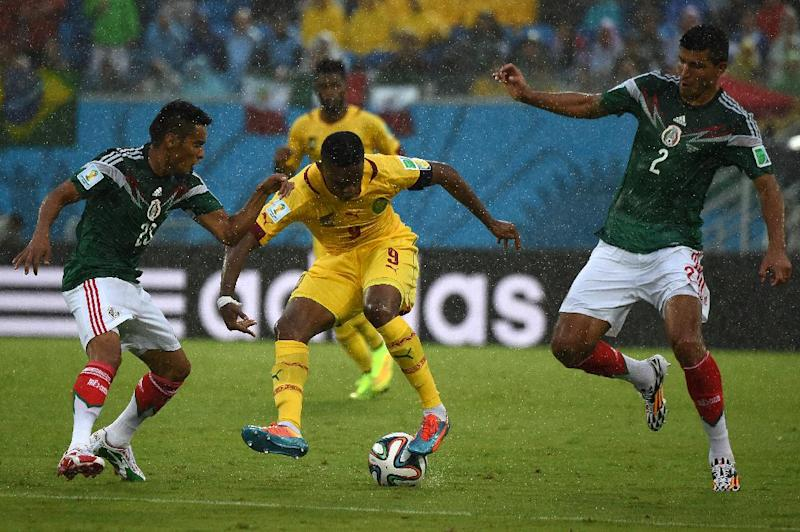 Cameroon's forward and captain Samuel Eto'o (C) fights for the ball during a 2014 FIFA World Cup match in Natal, Brazil on June 13, 2014 (AFP Photo/Christophe Simon)