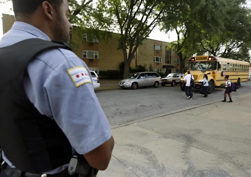 "A Chicago Police officer patrolling the neighborhood watches school children board a buss outside Gresham Elementary School on the first day of classes Monday, Aug. 26. 2013 in Chicago. Thousands of students will travel newly designated ""Safe Passage"" routes after CPS announced in May it would close about 50 schools and programs. Workers hired to help students get to and from school safely will be stationed along those routes, as well as police, firefighters and even public library security guards. (AP Photos/M. Spencer Green)"