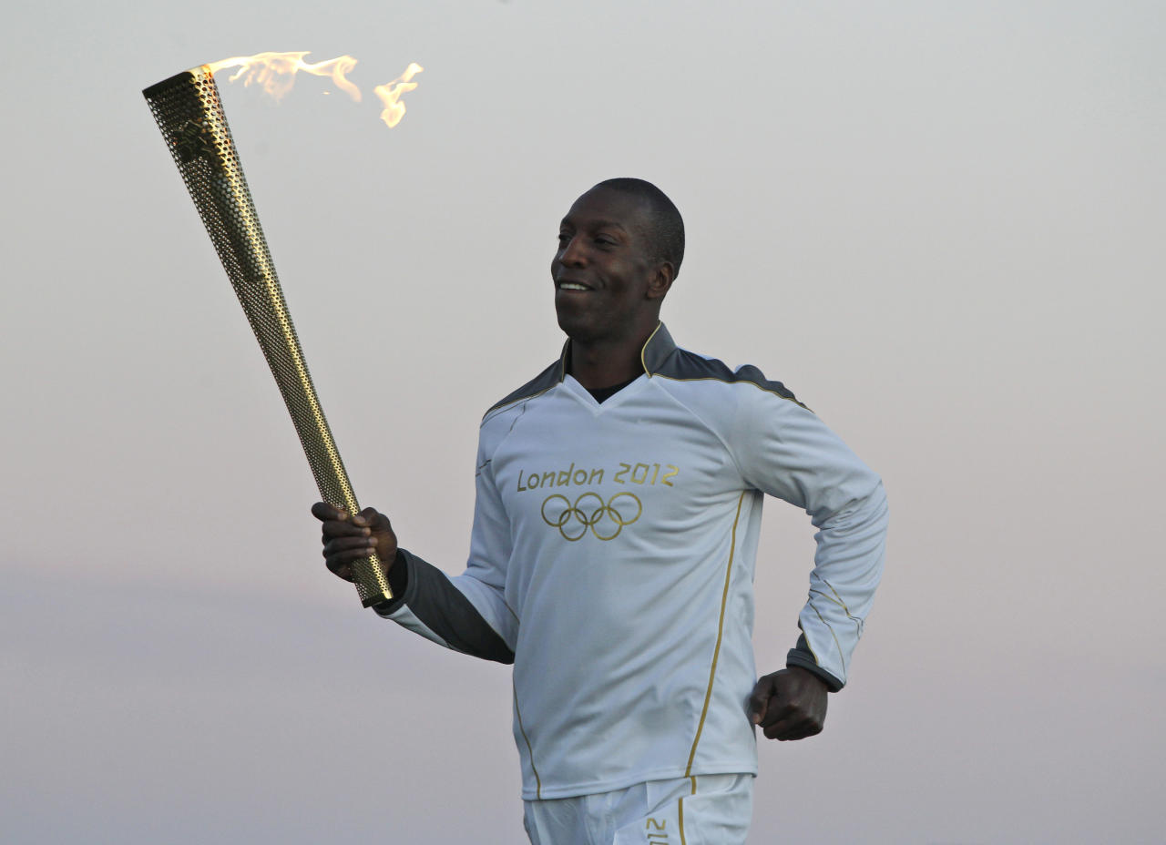 U.S. Olympian sprinter Michael Johnson runs holding the Olympic Flame at Stonehenge, England, Thursday, July 12, 2012. Johnson, who won four Olympic gold medals and eight world championship gold medals, currently holds the world and Olympic records in the 400 meters and 4 x 400 meters relay. The Olympic Torch is being carried around England in a relay of torchbearers to make its way to the London 2012 Olympic Games opening ceremony. (AP Photo/Lefteris Pitarakis)