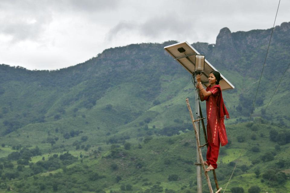 A woman standing on a ladder making adjustments to a solar panel