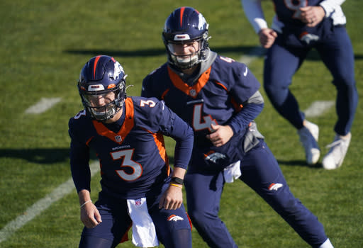 Denver Broncos quarterbacks Drew Lock, front, and Brett Rypien take part in drills during an NFL football practice at the team's heasdquarters Wednesday, Nov. 25, 2020, in Englewood, Colo. (AP Photo/David Zalubowski)