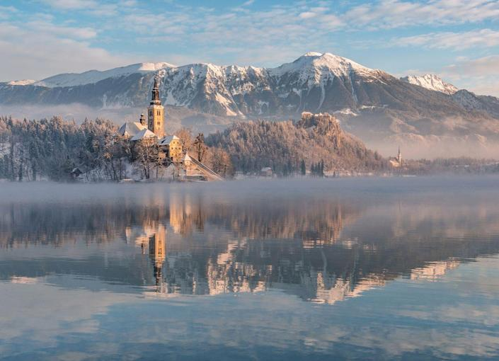 <p>A crisp winter fog rolls over Lake Bled in the Julian Alps region of Slovakia.</p>