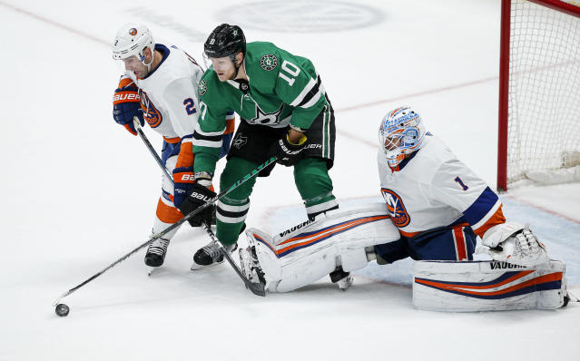 Dallas Stars forward Corey Perry (10) works between New York Islanders defenseman Nick Leddy (2) and goaltender Thomas Greiss (1) for the puck during the second period of an NHL hockey game Saturday, Dec. 7, 2019, in Dallas. (AP Photo/Brandon Wade)