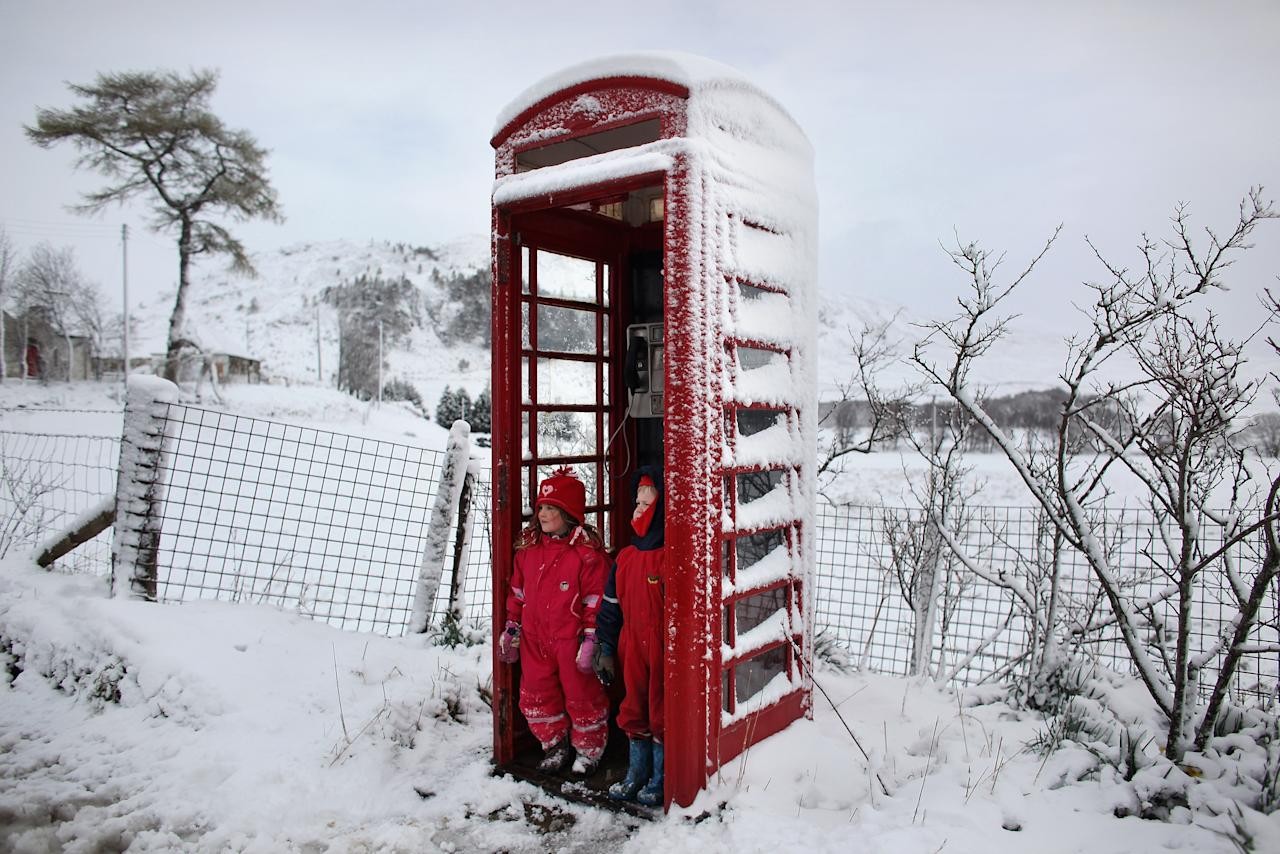 BRAEMAR, SCOTLAND - APRIL 03:  Nina Padmanabhan and Murray Waugh shelter from the cold in a red telephone box following a sledging trip on April 3, 2012 in Braemar, Scotland. Snow has returned to parts of Scotland just a week after the country experienced record high temperatures for March. (Photo by Jeff J Mitchell/Getty Images)
