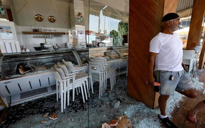 An Israeli man stands at a restaurant that was attacked the previous night in Israel's Mediterranean city of Bat Yam - AFP
