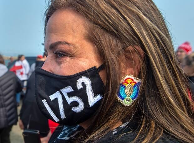 A woman wears a face mask honouring the Treaty of 1752 as members of the Sipekne'katik First Nation and others attend a ceremony on the wharf in Saulnierville, N.S., to bless the fleet before it launches its own self-regulated fishery on Thursday, Sept. 17, 2020.