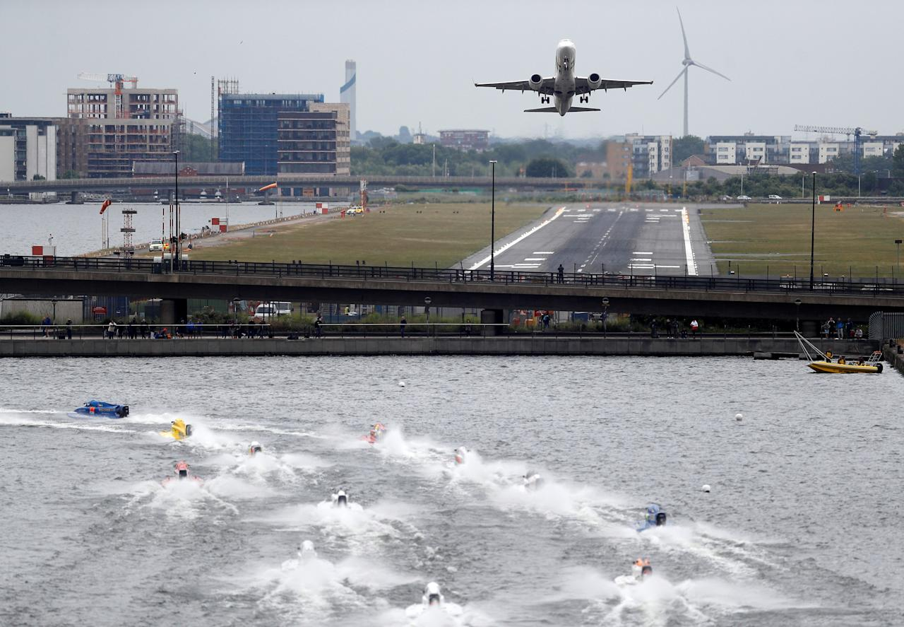 F1 powerboats race across the water, as an aeroplane takes off from City Airport in the background, in the F1H20 London Grand Prix in the Royal Victoria Dock in London, Britain, June 17, 2018. REUTERS/Peter Nicholls