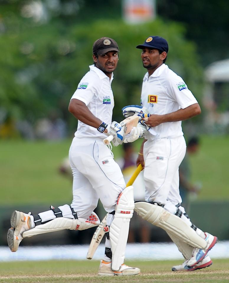 Sri Lankan batsmen Tillakaratne Dilshan (R) and Kumar Sangakkara (L) run between the wickets during the fourth day of their opening Test match between Sri Lanka and Bangladesh at the Galle International Cricket Stadium in Galle on March 11, 2013. Bangladesh were bowled out for 638 in their first innings in reply to Sri Lanka's 570-4 declared on the fourth day of the opening Test in Galle on Monday. AFP PHOTO/ LAKRUWAN WANNIARACHCHI        (Photo credit should read LAKRUWAN WANNIARACHCHI/AFP/Getty Images)