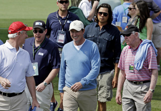 Former professional hockey player Wayne Gretzky, center, walks along the second fairway during the second round of the Masters golf tournament Friday, April 11, 2014, in Augusta, Ga. (AP Photo/David J. Phillip)