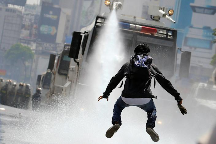 <p>MAY 26, 2017 – A demonstrator jumps away from a jet of water released from a riot security forces vehicle during a rally against Venezuela's President Nicolas Maduro in Caracas, Venezuela. (Photo: Carlos Barria/Reuters) </p>