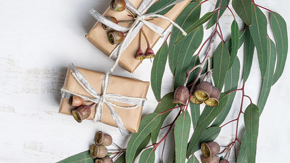 Wholesome gifts wrapped in natural paper with twine,silver ribbon and decorated with eucalyptus leaves and gum nuts. Photo: Getty Images.