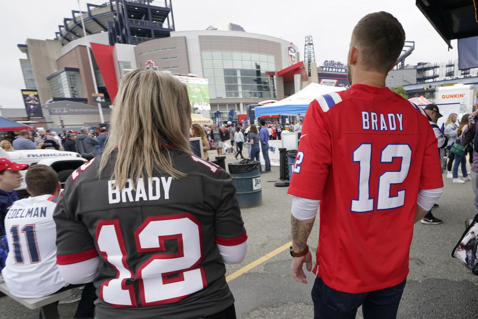 Melissa Zaske, left, of Vancouver, wears Tom Brady's current Tampa Bay Buccaneers jersey while walking with her husband Derek, who wears Tom Brady's old New England Patriots jersey, prior to an NFL football game between the New England Patriots and Tampa Bay Buccaneers, Sunday, Oct. 3, 2021, in Foxborough, Mass. (AP Photo/Steven Senne)