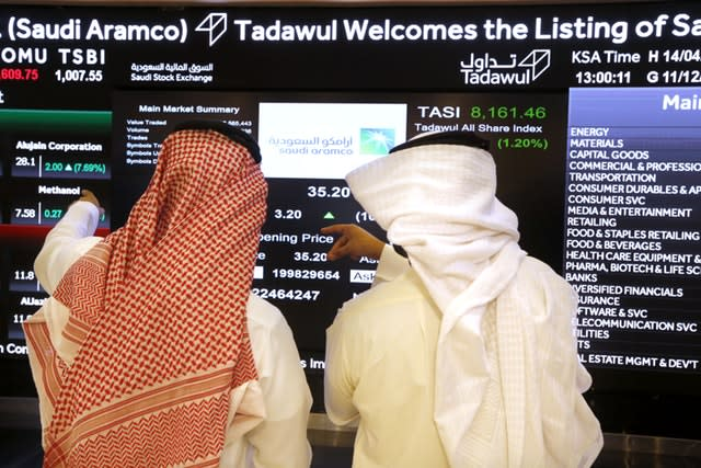 Saudi stock market officials watch the market screen