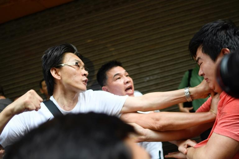 In some neighbourhoods like North Point, scuffles have broken out between pro-Beijing supporters (L) and protesters or media (AFP Photo/Manan VATSYAYANA)