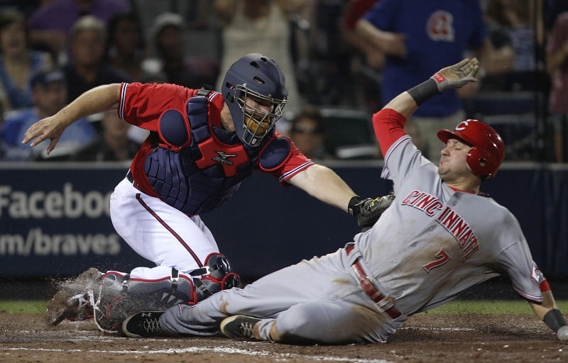 Cincinnati Reds' Paul Janish, right, is tagged out at home plate by Atlanta Braves catcher David Ross on a hit by Cincinnati Reds' Brandon Phillips, not pictured, in the eighth inning of a baseball game Sunday, May 29, 2011 in Atlanta. (AP Photo/David Goldman)