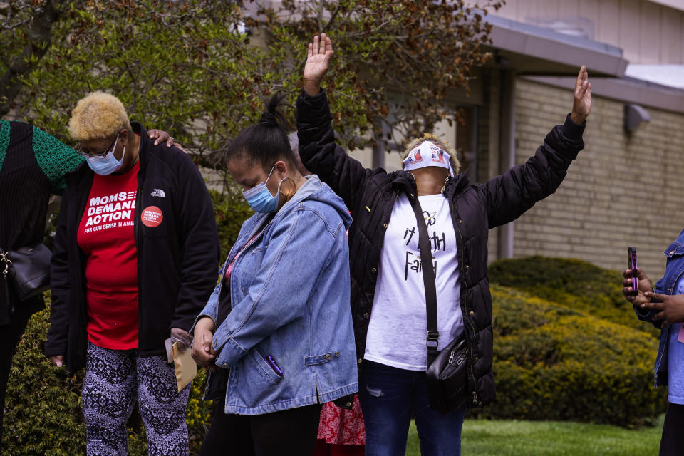 Connie Nance raises her arms in prayer during a vigil at the Olivet Missionary Baptist Church in Indianapolis, Saturday, April 17, 2021 for the victims of the shooting at a FedEx facility. A gunman killed eight people and wounded several others before taking his own life in a late-night attack at a FedEx facility near the Indianapolis airport, police said. (AP Photo/Michael Conroy)
