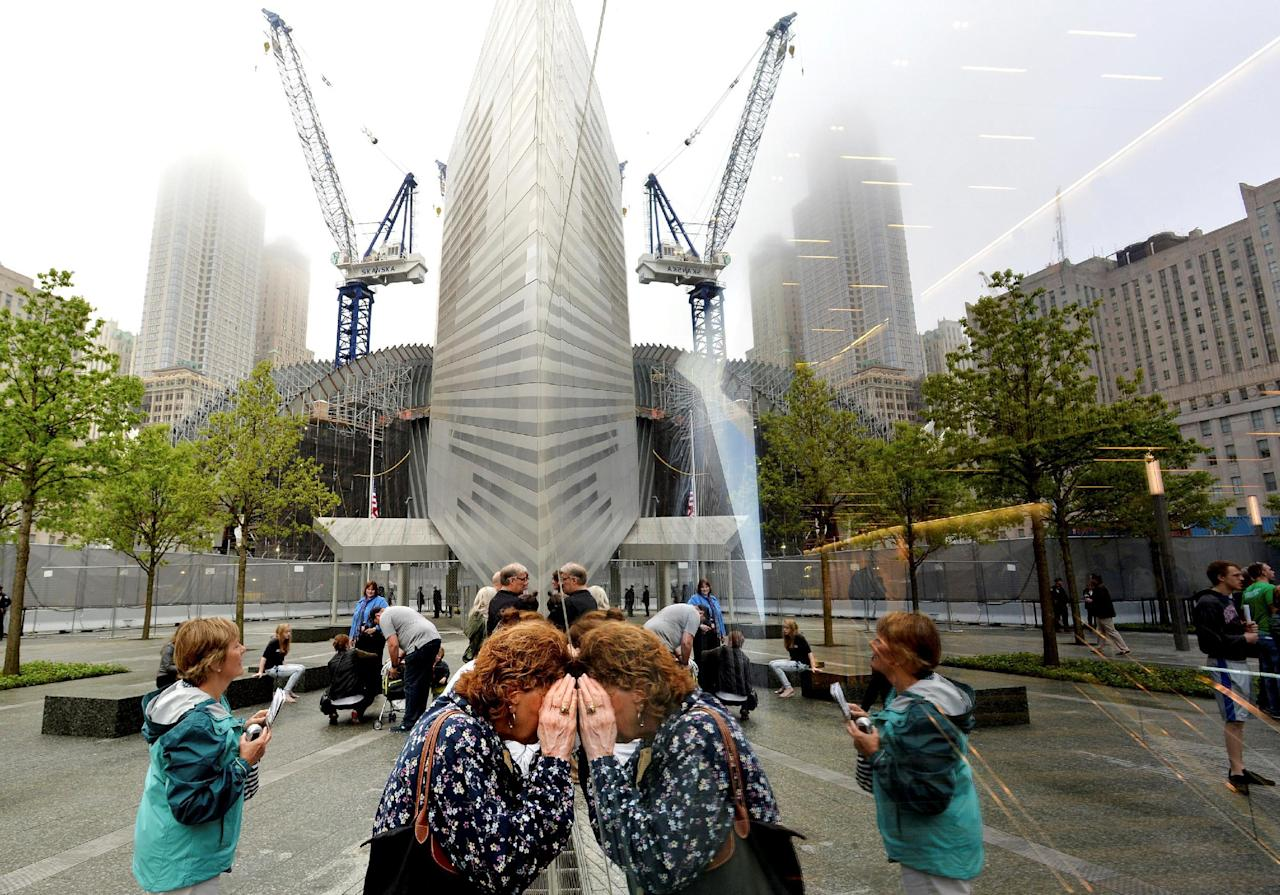FILE PHOTO:  People try to look through the windows of the National September 11 Memorial Museum during the museum's dedication in New York, New York, U.S. on May 15, 2014. REUTERS/Justin Lane/Pool/File Photo