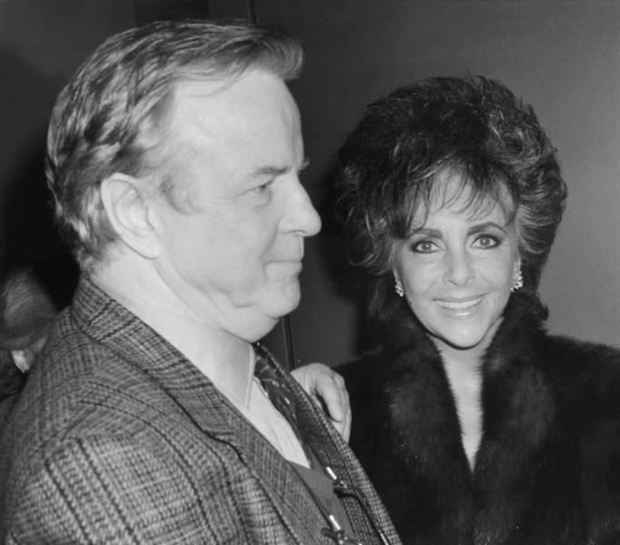 """FILE - In this April 10, 1987 file photo,Franco Zefferelli, producer and set designer of the Puccini opera """"Turandot,"""", escorts Liz Taylor to her limousine after the performance. Italian director Franco Zeffirelli, famed for operas, films and television, has died in Rome at the age of 96. Zefffirelli's son Luciano said his father died at home at noon on Saturday. (AP Photo/Frankie Ziths, File)"""