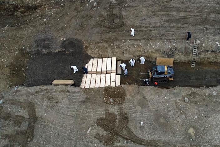Workers wearing personal protective equipment bury bodies in a trench on Hart Island in the Bronx borough of New York. The death toll from the coronavirus in New York City is nearly half that of the entire country.