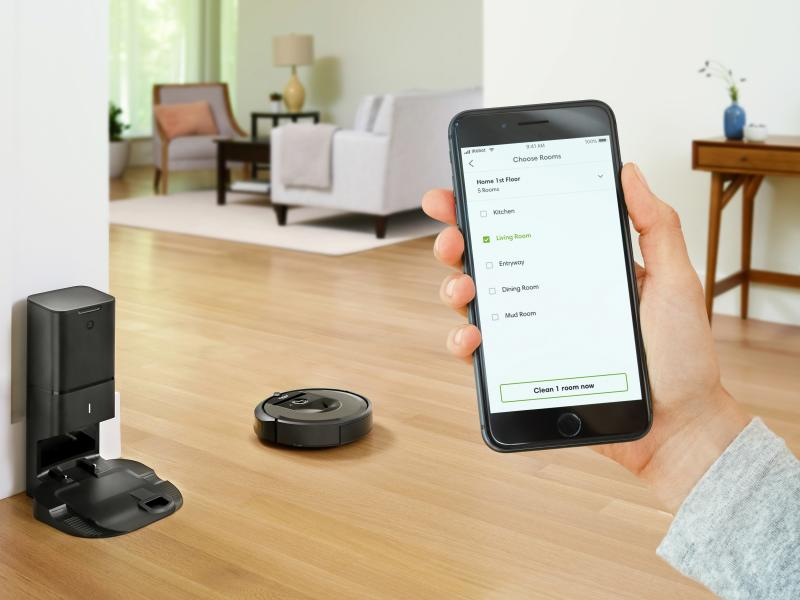 Hand holding phone with iRobot HOME app open and Roomba running in the background, in the living room