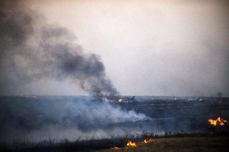 Smoke billows from the flaming debris of a crashed Ukrainian fighter jet near the village of Zhdanivka, some 40 kilometres northeast of the rebel stronghold of Donetsk, eastern Ukraine, on August 7, 2014