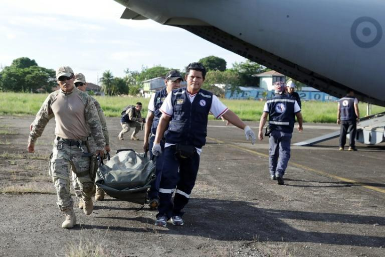 Military personel and members of a health brigade unload equipment from a plane, to be used in areas affected by a quake, in Yurimaguas in Peru's Amazon region