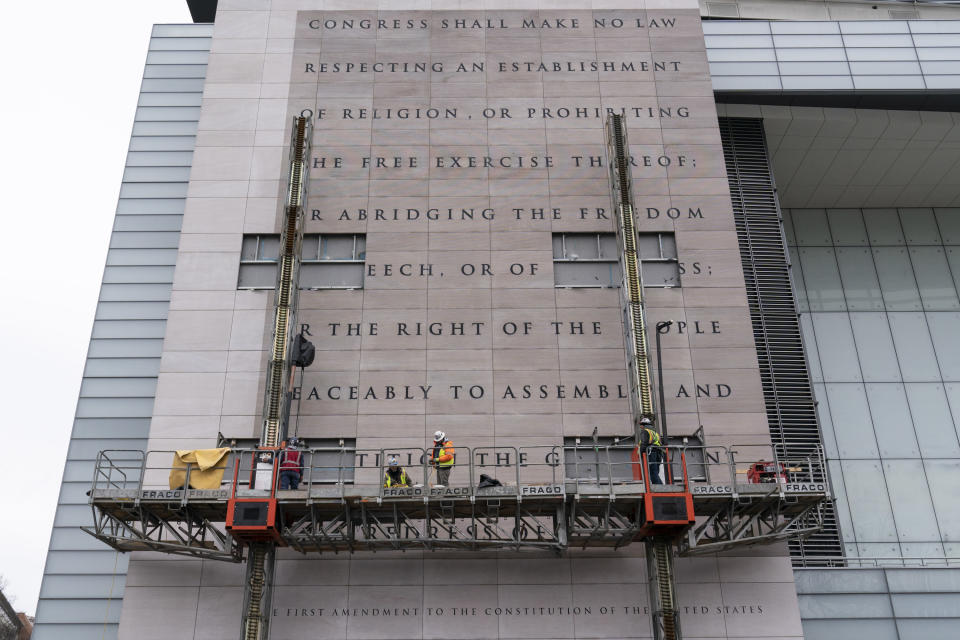 FILE—This file photo from Feb. 12, 2021, workers remove the facade bearing the First Amendment of the U.S. Constitution from what was formerly the Newseum, a private museum dedicated to exploring modern history as told through the eyes of journalists, along Pennsylvania Avenue, in Washington. The façade will be reinstalled at The National Constitution Center in Philadelphia. (AP Photo/Alex Brandon, File)