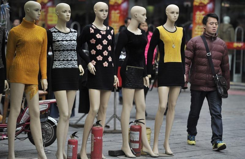 A man walks past mannequins at a wholesale market in Hefei