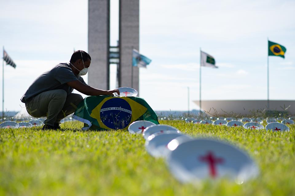 BRASILIA, BRAZIL - FEBRUARY 2: A Rio da Paz member fixes the Brazilian flag during an installation of white plates with a red cross in favor of the return of emergency aid from the government amidst the coronavirus pandemic in front Brazilian Congress on February 02, 2021 in Brasilia. There are 594 plates painted with red crosses, each representing a member of the National Congress. Brazil has over 9,229,000 confirmed positive cases of Coronavirus and has over 225,099 deaths. (Photo by Andressa Anholete/Getty Images)