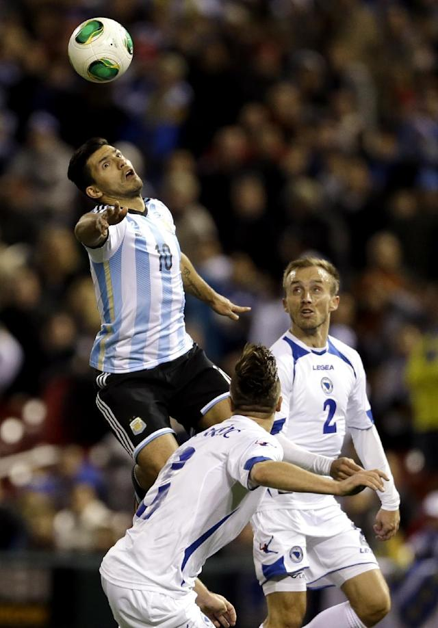 Argentina's Sergio Aguero (10) heads the ball as Bosnia's Ermin Bicakcic and Avdija Vrsajevic (2) defend during the first half of an international friendly soccer match Monday, Nov. 18, 2013, in St. Louis. Aguero scored both goals in Argentina's 2-0 victory. (AP Photo/Jeff Roberson)