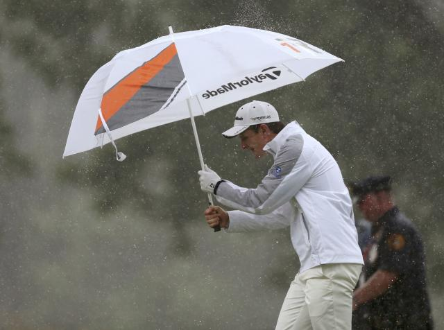 England's Justin Rose walks under an umbrella on the 14th fairway during the final round of the 2013 U.S. Open golf championship at the Merion Golf Club in Ardmore, Pennsylvania, June 16, 2013. REUTERS/Adam Hunger (UNITED STATES - Tags: SPORT GOLF ENVIRONMENT)