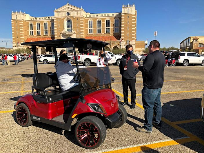 A group of tailgaters talk with a man sitting in a red golf cart