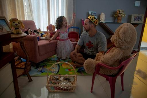Nurse Hans Bossan plays with his daughter after his shift at one of his three jobs assisting patients infected with the novel coronavirus (COVID-19), at their house in Sao Goncalo, Rio de Janeiro state, Brazil, on June 3, 2020