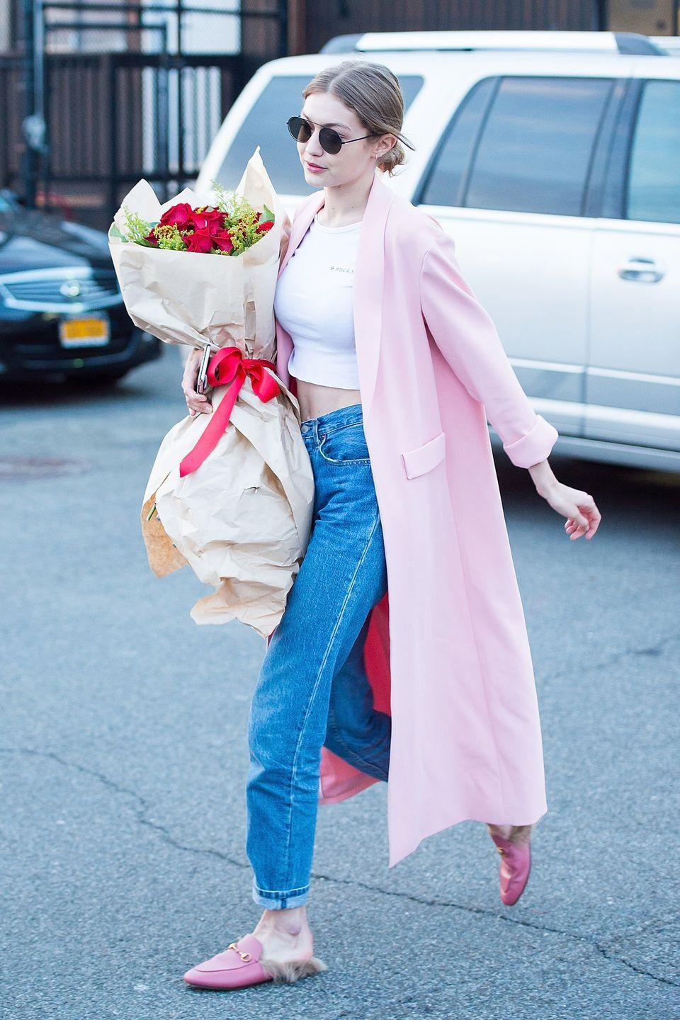 """<p>In a cropped Bella Hadid x Chrome Hearts white tee under an <a href=""""https://www.aliceandolivia.com/angela-long-coat.html"""" rel=""""nofollow noopener"""" target=""""_blank"""" data-ylk=""""slk:Alice + Olivia pink duster coat"""" class=""""link rapid-noclick-resp"""">Alice + Olivia pink duster coat</a> with vintage Levi's jeans, pink leather Gucci slippers and black L.G.R. Tuareg aviator sunglasses while out in New York City on her birthday. </p>"""