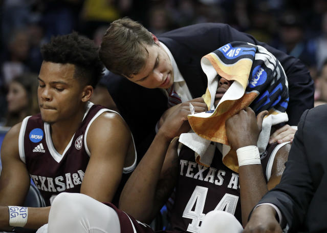 Texas A&M forward Robert Williams, right, covers his face with a towel on the bench during the second half of the team's NCAA men's college basketball tournament regional semifinal against Michigan on Thursday, March 22, 2018, in Los Angeles. (AP Photo/Jae Hong)