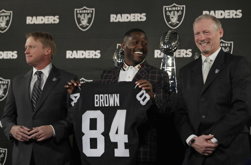 Oakland Raiders wide receiver Antonio Brown, center, holds his jersey beside coach Jon Gruden, left, and general manager Mike Mayock back in March. (AP)