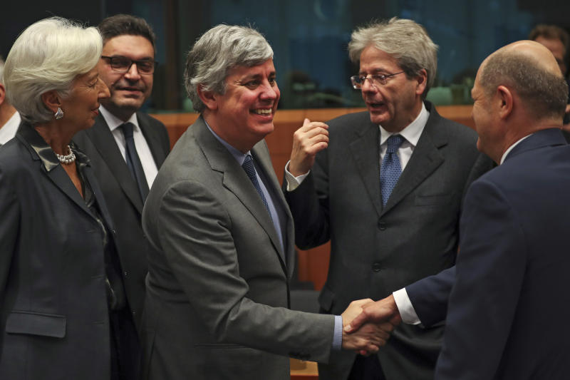 "FILE - In this Monday, Jan. 20, 2020 file photo Eurogroup President Mario Centeno, center, shakes hands with German Finance Minister Olaf Scholz, right, next to European Central Bank President Christine Lagarde, left, Cyprus' Economy Minister Constantinos Petrides, second left, and European Commissioner for Economy Paolo Gentiloni, second right, during a meeting of European Union Finance Ministers in Eurogroup format at the Europa building in Brussels. Governments from the 19 countries that use the euro overcame sharp differences to agree Thursday on measures that could provide more than a half-trillion euros ($550 billion) for companies, workers and health systems to cushion the economic impact of the virus outbreak. Mario Centeno, who heads the finance ministers' group from euro countries, called the package of measures agreed upon ""totally unprecedented... Tonight Europe has shown it can deliver when the will is there."" (AP Photo/Francisco Seco, File)"